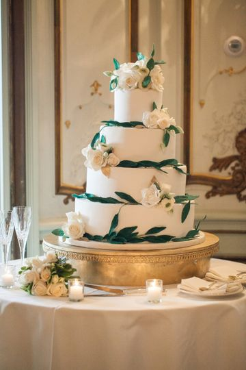 Matte ivory fondant adorned with dark green sugar leaves and ivory sugar roses.  Photography by Sara...