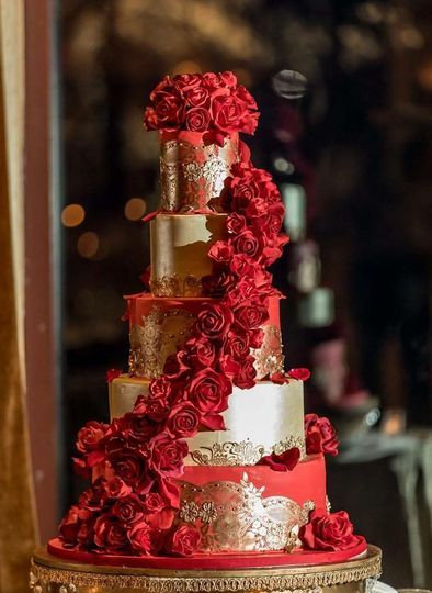 Red and gold wedding cake with red sugar flowers cascade