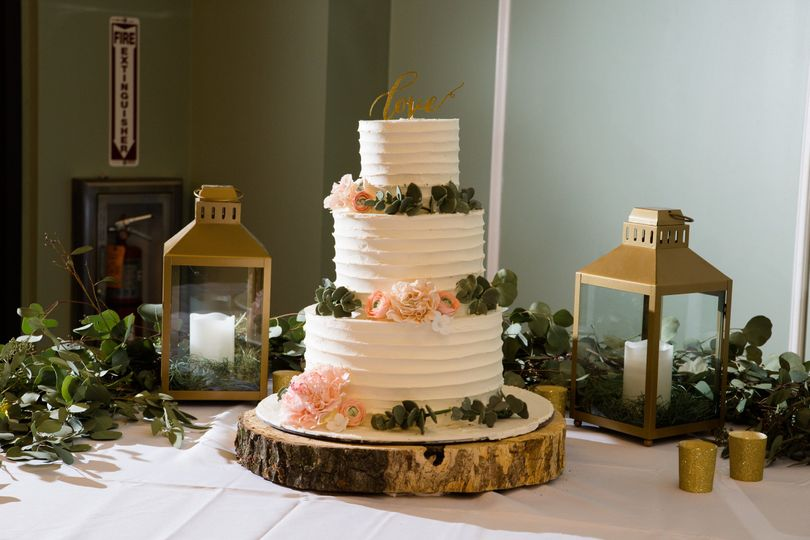 Textured wedding cake with sugar flowers of peonies, ranunculus, and eucalyptus.  Photography by...