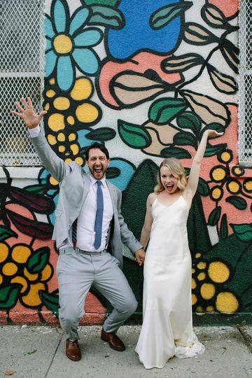 Newlyweds pose by mural