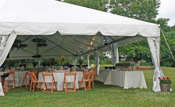The tent sides are pulled back to allow guests to enjoy the beauty of the afternoon in this backyard...