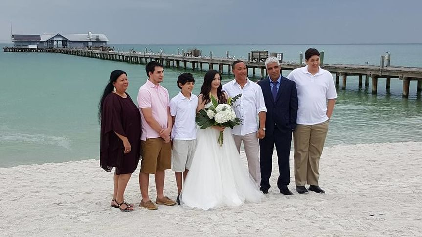 Newlyweds and family by the beach