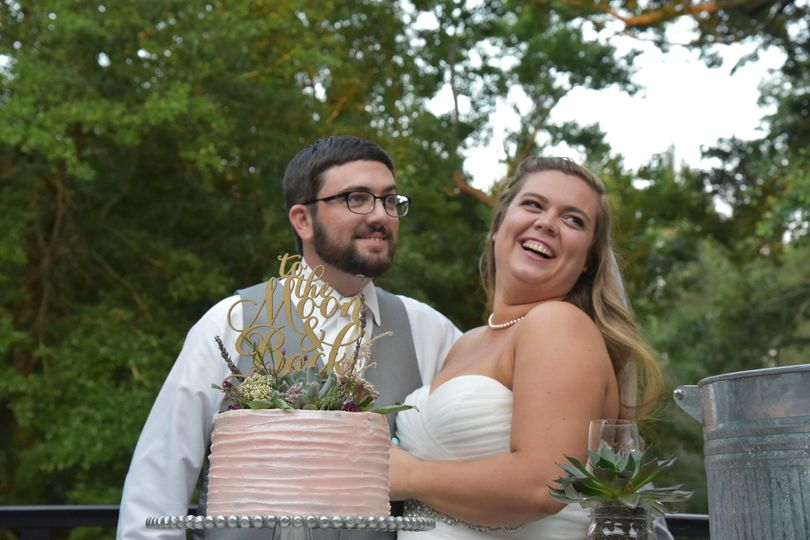 Groom and bride by the wedding cake