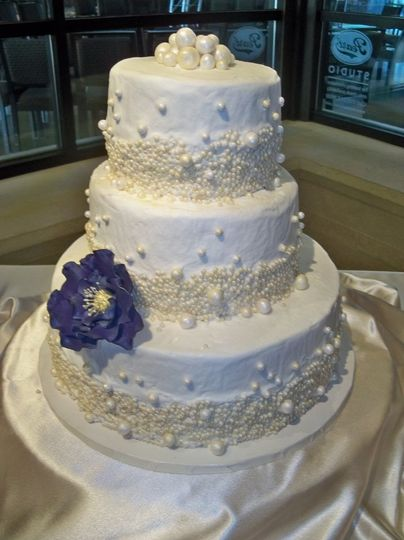 All white wedding cake with a blue flower