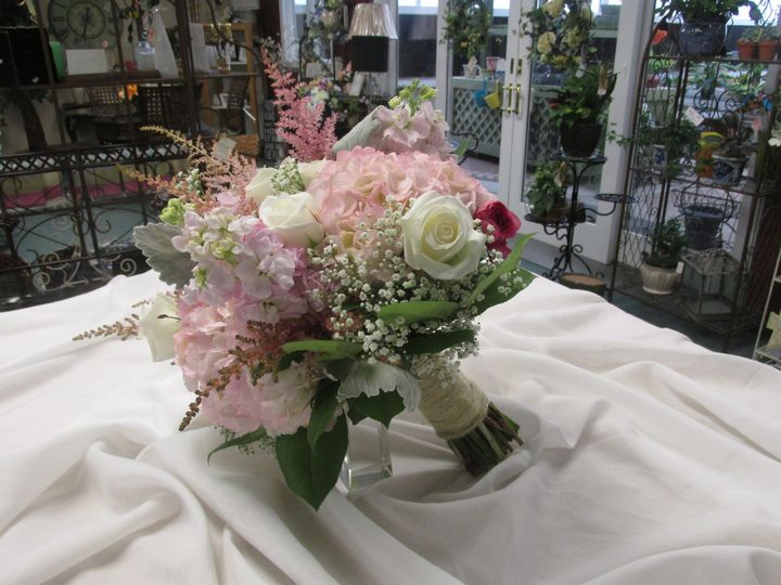 This lovely bridal bouquet consists of pink hydrangea and stock, white roses and babies breath and...