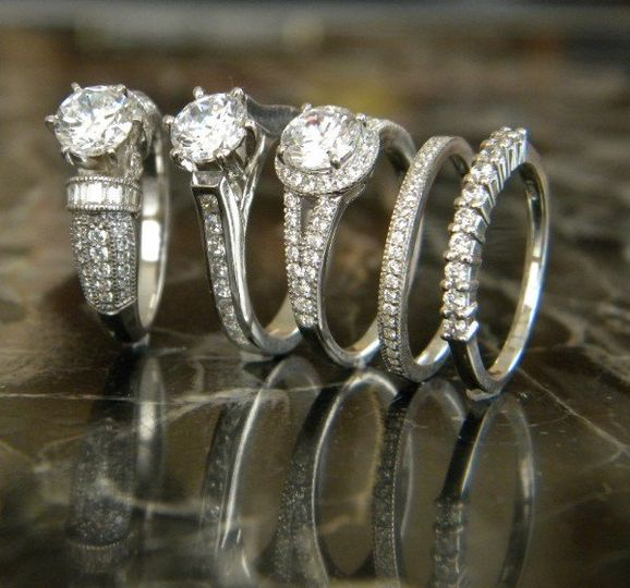 Diamond engagement rings with side accent diamonds and wedding bands in platinum and white gold.