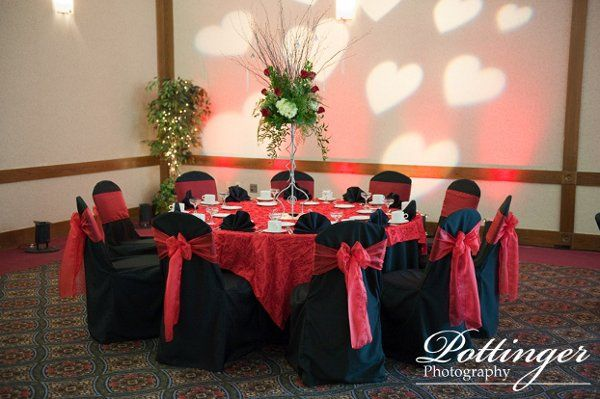Black chair covers with red organza sashes.  Red Abigail overlay with black poly floor length Linen....