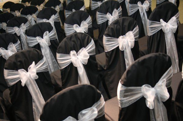 Black poly chair covers with white organza sashes.  Photo taken at Nathaniel Greene Lodge.