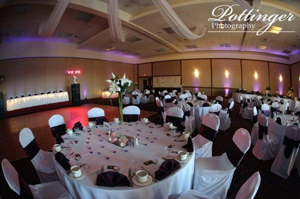 White linen and chair covers with eggplant napkins and sashes.  Photography by Pottinger at the...