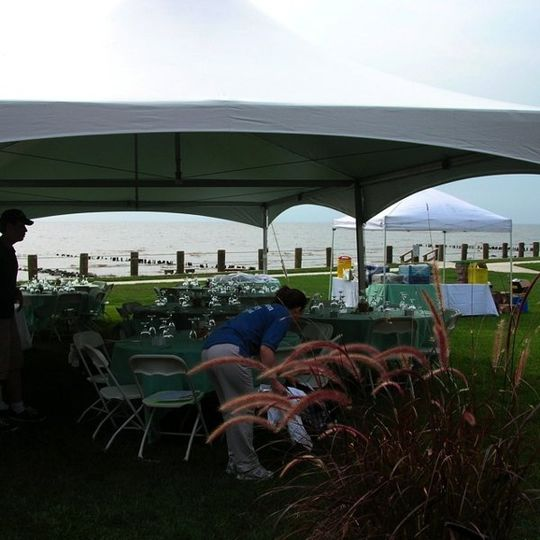 Caterers set up for a wedding reception at a private home on the beach.
