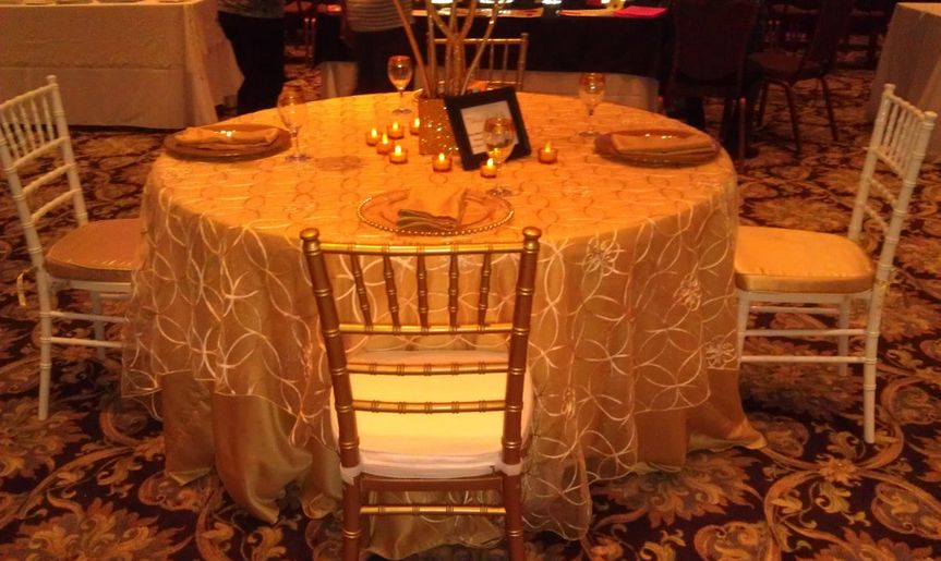Gold Ribbon Sheer Overlay with Gold Lamour Satin Tablecloth & Napkins and Gold/White Chivari Chairs