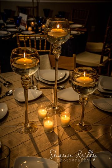Candle inside the tall glass table centerpiece