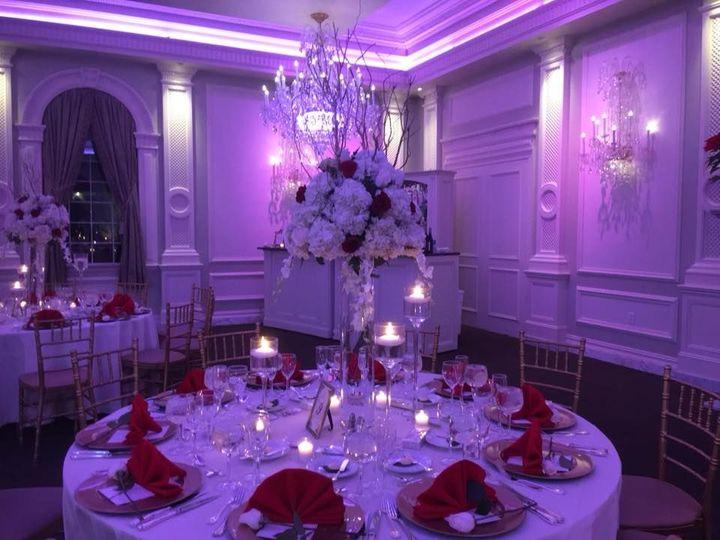 Pink uplights and candlelit table setup