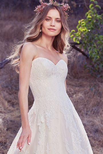 Olea		Cascades of breathtaking lace motifs elevate this timeless A-line, featuring a subtle...