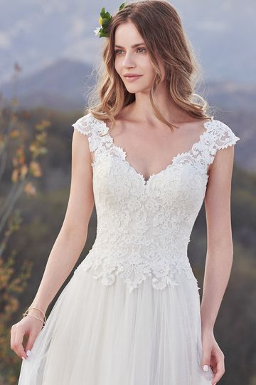 Hensley		Classic and demure, this tulle A-line features a lace bodice adorned with shimmering...