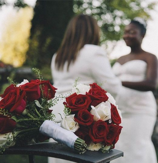 Newlyweds behind rose bouquet