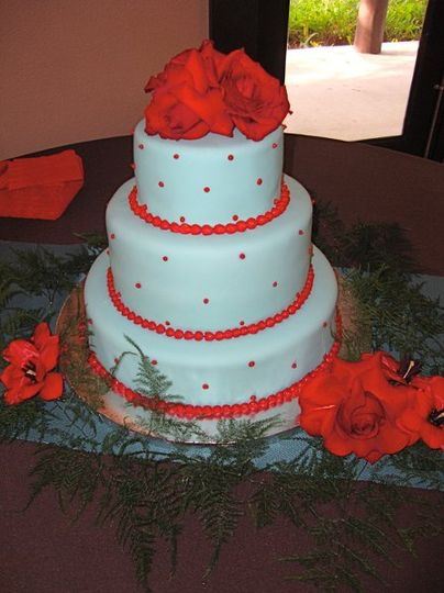 Teal and red fondant covered cake with small red dot accents and live roses and table decorations.