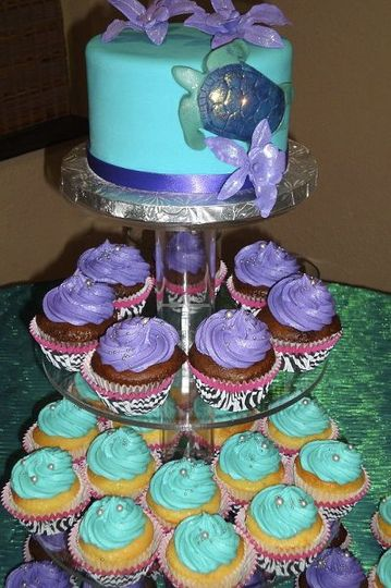 """Cupcake tower with 6"""" teal fondant covered cake with sea turtle and orchids.  Cupcakes in zebra..."""