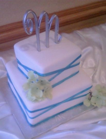 White square fondant covered wedding cake with teal criss cross ribbon and silver monogram cake top.