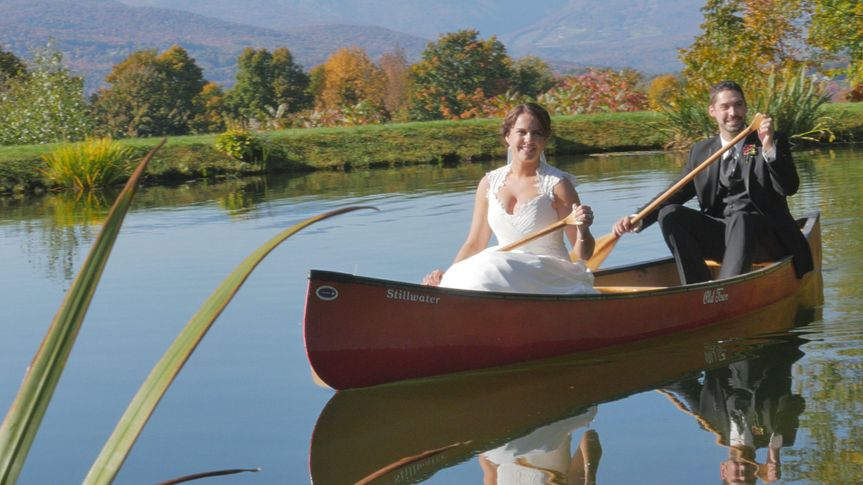 Bride and groom pose in canoe