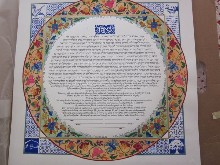 It is a circle within a square with paper-cut like details highlighting interests of the couple.