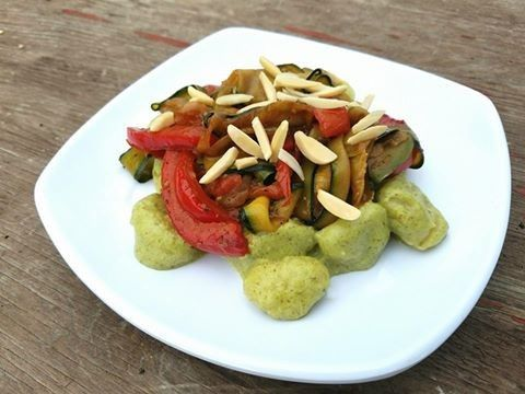 Creamy pesto gnocchi with roasted vegetables and garnished with almonds.