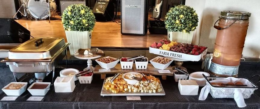 An appetizer display of our cheeseboard, fruit platter, scratch lemonade, and hand breaded chicken...