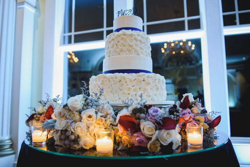 Multiple layered wedding cake surrounded by flowers