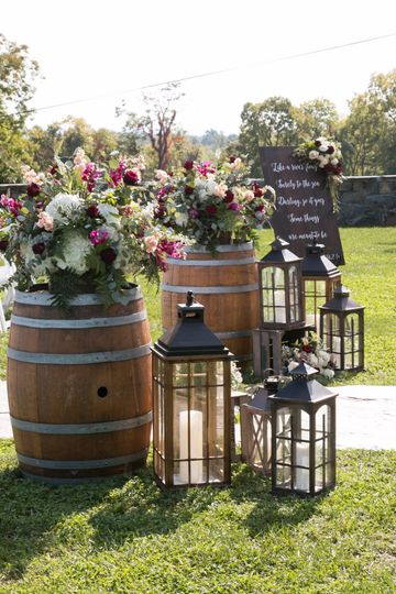Beautiful arrangements atop wine barrels to at the start of the aisle for this gorgeous vineyard...