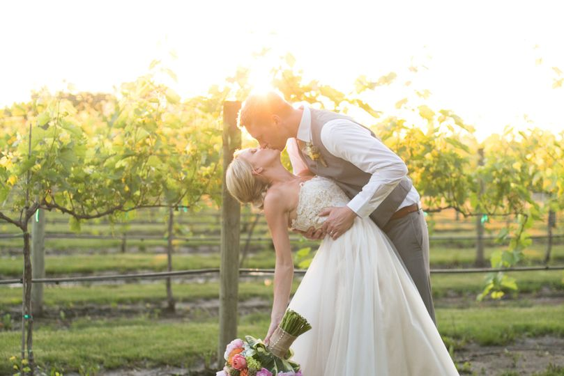 A romantic kiss in the vineyard as the sun is setting
