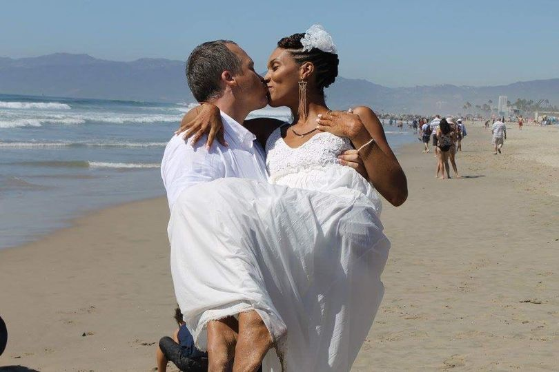Groom lifting and kissing his bride at the beach