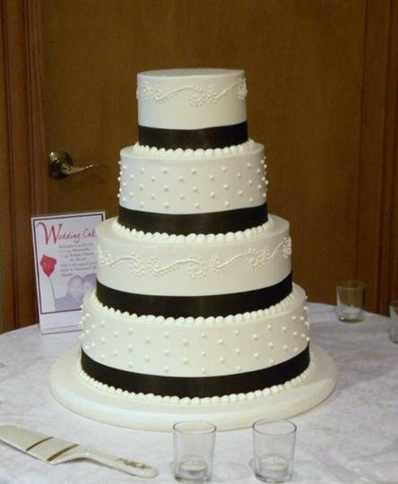 4 tiered buttercream with swiss dot and scroll design, chocolate brown satin ribbon trim