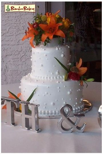 2 tiers wedding cake with whip cream icing and butter cream decor.