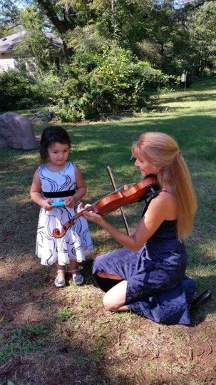Violinist playing for a child