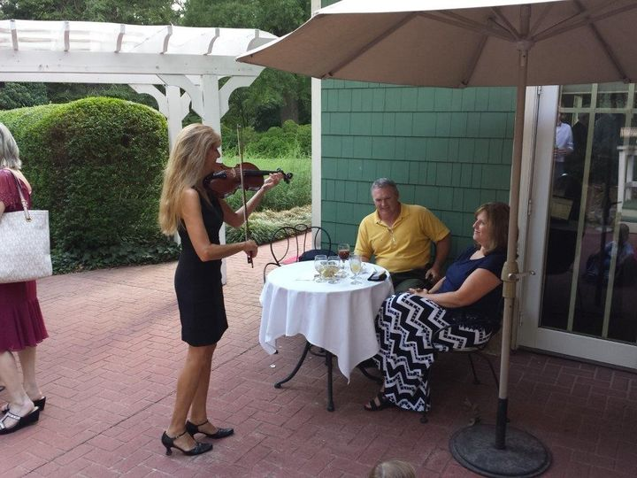 Violinist performing for an elderly couple