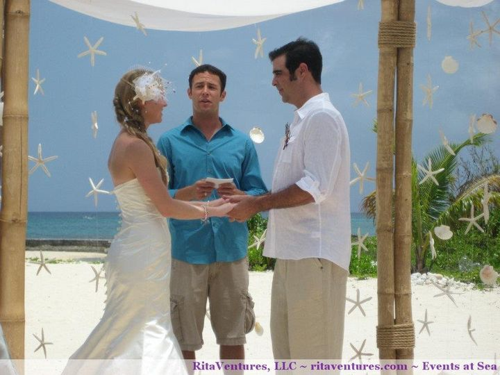 Beautiful view of the bride and groom underneath the bamboo canopy with hanging shells and starfish.
