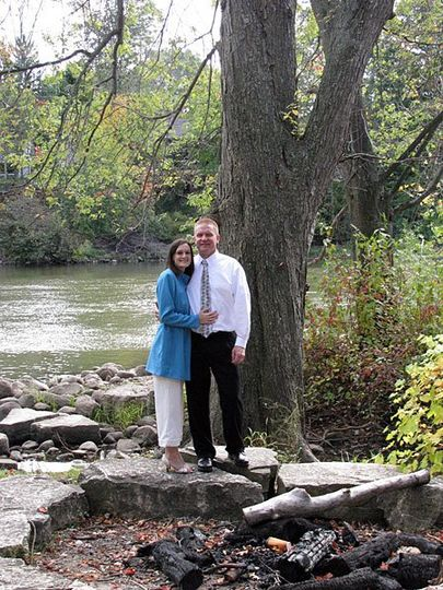 Kurt and Susan pose for after wedding photos by the river at Leslie Tassle Park in Grand Rapids,...