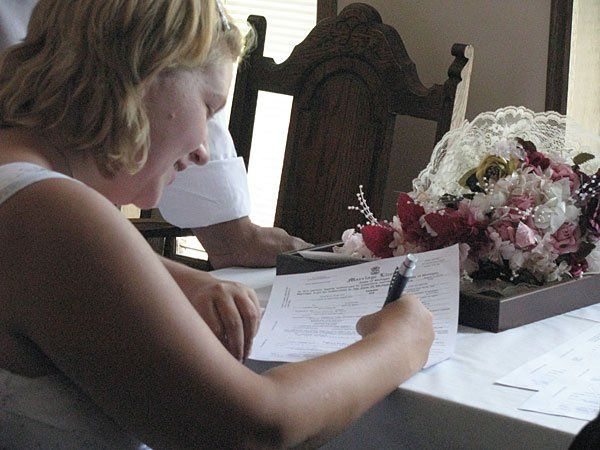 April and Esteban sign their marriage license at the GRWeddingOfficiant. wedding chapel in Grand...