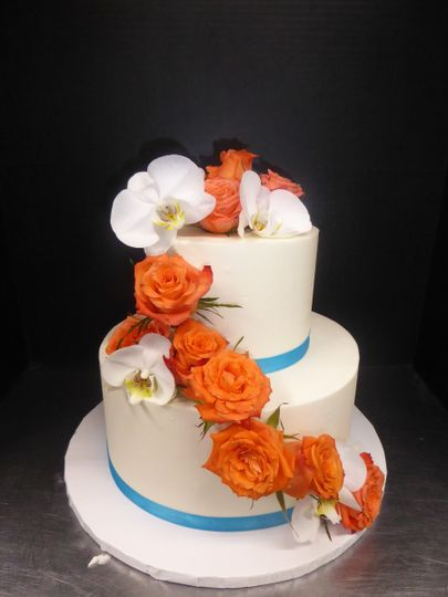 Simple 2 tier buttercream with fresh orange roses and moth orchids