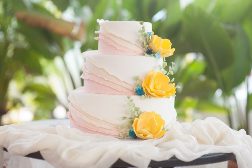 3 tier fondant with blush ruffles, yellow and blue sugar flowers