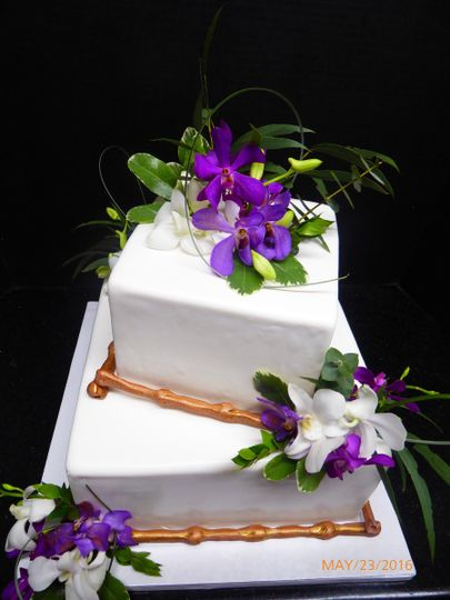 2 tier offset square fondant cake with sugar bamboo and fresh purple flowers and greenery.