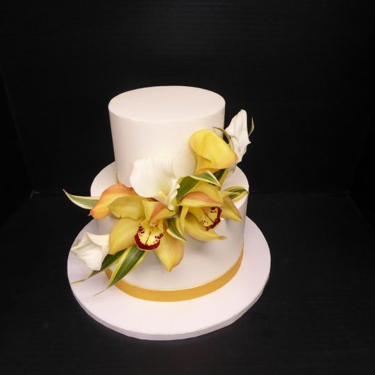 Simple 2 tier buttercream with fresh yellow Cymbidium and Calla lily flowers