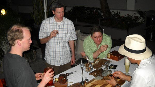 Guests at a bachelor party enjoy one of our cigar rollers making cigars by hand while he explains a...