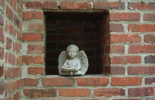 A stone cherub tucked into a nook off the Manor's terrace.
