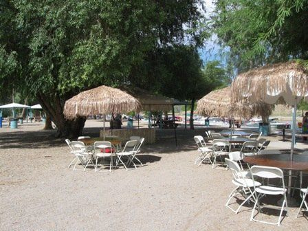 Palapa covered umbrellas for guest seating in London Bridge Beach Park