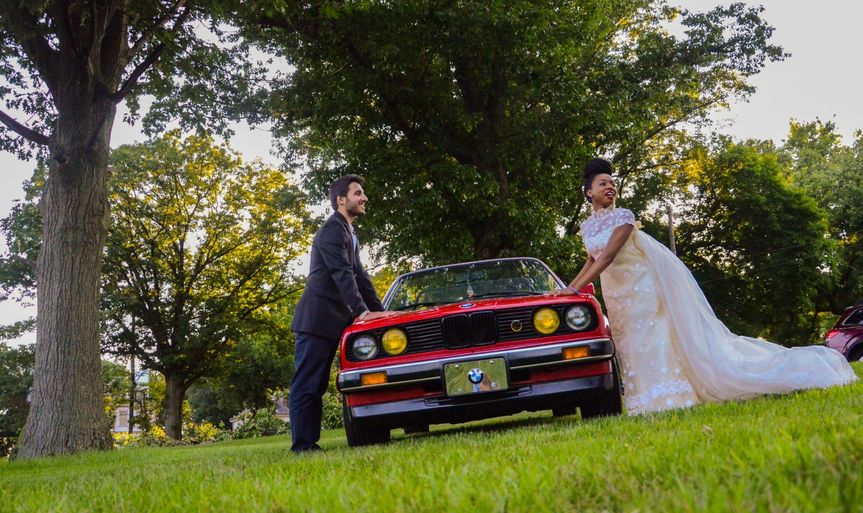 Couple posing beside car