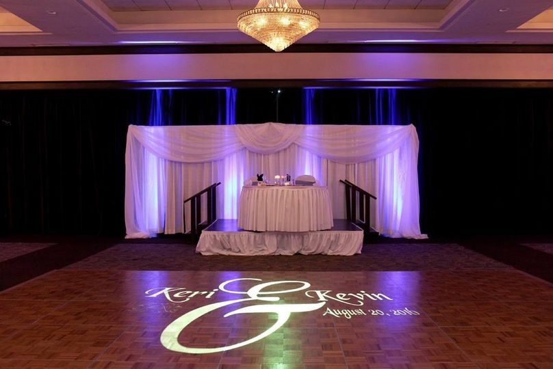A projected monogram on the dancefloor with uplights in the color of the bridesmaids dresses make a...