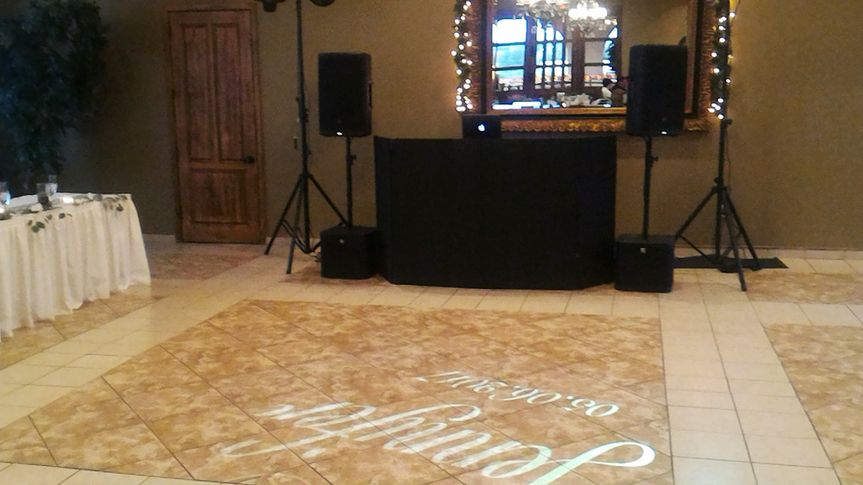 Monogram of couples name and wedding date projected onto the dance floor. This enhances the feel of...