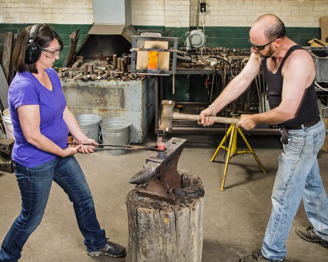 Nicole and Harry hammering hot steel.