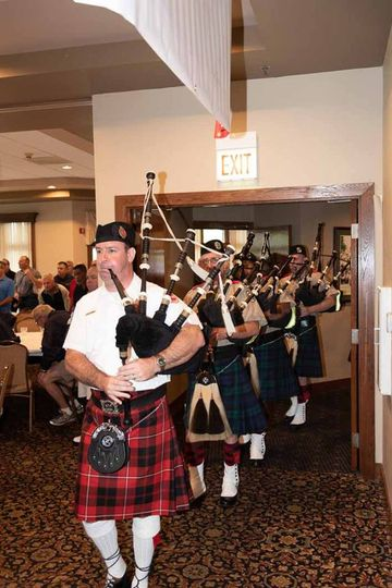 Bagpiper leading a band